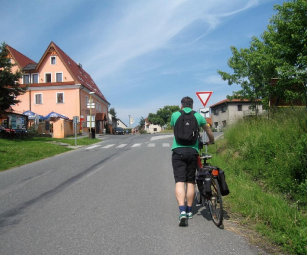 Osoba vedoucí jízdní kolo jde po správné straně vozovky